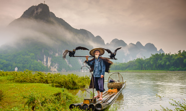Китай. Горы Гуйлинь. Cormorant fisherman and his birds on the Li River in Yangshuo, Guangxi, China. Фото sepavone - Depositphotos