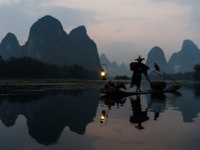 Китай. Горы Гуйлинь. Fisherman fishing  with cormorant Li river, between Guilin and Yangshuo in Guangxi province  China. Фото STYLEPICS - Depositphotos