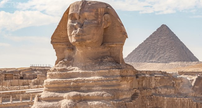 Египет. Гиза. Большой сфинкс. Sphinx monument against the background of large pyramids on a sunny day. Фото leshiy985-Depositphotos