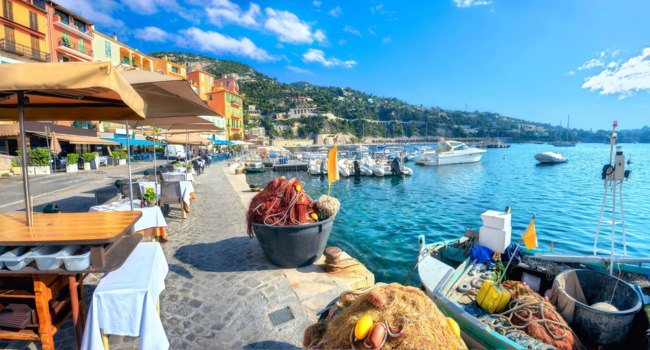 Лазурный берег Франции. Вильфранш. Panoramic cityscape with cafe and fishing boat in resort town Villefranche sur Mer. Cote d'Azur, France. Фото Bareta-Deposit