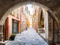 Лазурный берег Франции. Narrow cobblestone street with buildings though stone arch in Villefranche-sur-Mer on French Riviera, France. Фото elenathewise-Deposit