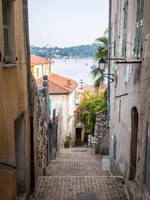 Narrow street with old buildings leading to Mediterranean sea in medieval town Villefranche-sur-Mer on French Riviera, France. Фото elenathewise - Depositphotos
