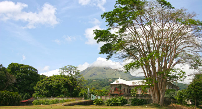 Клуб путешествий Павла Аксенова. Франция. Остров Мартиника. Martinique landscape with a plantation house & volcano in the background, Martinique, Caribbean, France. Фото LisaStrachan - Deposit