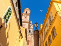 Франция. Ментон. Belfry of Saint-Michel Archange basilica among colorful houses under blu sky in old town of Menton, France. Фото rglinsky - Deposit
