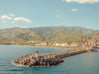 Заморские территории Франции. Остров Реюньон. A long breakwater in the port and big green hills, Le Port, Reunion. Фото Sam-714 - Depositphotos