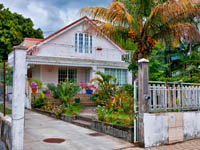 Заморские территории Франции. Остров Реюньон. View of brick house with red roof and yard of different flowers. Reunion Island. Фото zx6r92 - Depositphotos