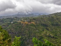 Заморские территории Франции. Остров Реюньон. Landscape of green forest with village on the top of mountain. Reunion island. Фото zx6r92-Depositphotos