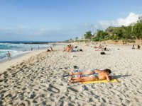 Остров Реюньон. eople sunbathing and swimming on the beach of Roches Noires on La Reunion island, France. Фото Fotoember-Depositphotos