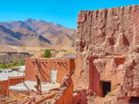 Иран. ДеThe ruined abandoned red adobe building in terrace Abyaneh village with picturesque Karkas mountains and ancient fort, Iran. Фото efesenko-D