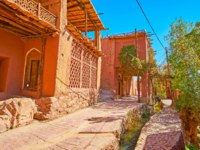 Walk the old street of historic Abyaneh village with reddish adobe houses, green gardens and narrow mountain stream, running along the road. Фото efesenko-Dep