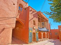 The narrow curved street of the oldest Iranian village, located on the slope of Karkas Mount and famous for its traditional red clay houses in Abyaneh. Фото efesenko-Dep