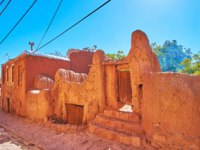 Иран. Деревня Абьяни. The medieval reddish mud fence with shabby wooden doors in the street of mountain Abyaneh village, Iran. Фото efesenko-Depositphotos