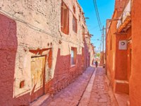 The narrow shady street of Abyaneh village with preserved old edifices of red-ochre mud and stones from Karkas montains, Iran. Фото efesenko - Depositphotos