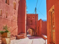 Walking down the old street with a view on reddish buildings and the ancient Harpak Fire Temple-the oldest monument in Abyaneh village, Iran. Фото efesenko-Deposit