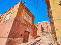Иран. Деревня Абьяни. The steep ascent street in medieval mountain village with red adobe houses on both sides, Abyaneh, Iran. Фото efesenko-Depositphotos