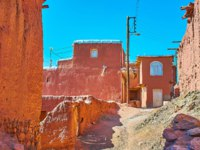 Иран. Деревня Абьяни. The scenic street of historic village with bright red clay buildings and narrow cwinding streets, Abyaneh, Iran. Фото efesenko-Depositphotos