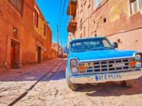 Иран. Деревня Абьяни. The vintage blue car is parked in medieval street of historic mountain village in Abyaneh. Фото efesenko-Depositphotos