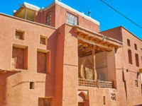 The facade of the old mosque of Abyaneh village with red adobe walls and the Nakhl wooden structure for Ashura ritual, standing on the terrace, Iran. Фото efesenko-Dep