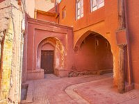 Иран. Деревня Абьяни. The curved village street runs through the old red house with arched pass, Abyaneh, Iran. Фото efesenko-Depositphotos