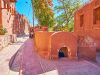 The old street of the terrace mountain village of Abyaneh with red adobe houses, lush green gardens and interesting ancient historic landmarks, Iran. Фото efesenko-Dep