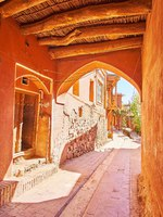 Иран. Деревня Абьяни. Walking through the narrow pass under the house with old log ceiling and red adobe walls, Abyaneh village, Iran. Фото efesenko-Deposit