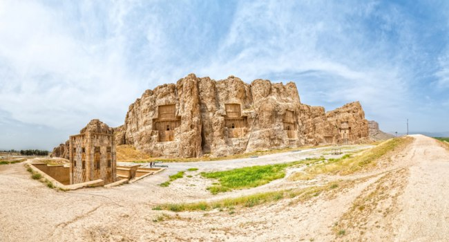 Иран. Накше-Рустам. Naqsh-e Rustam Panorama of the historical four tombs belonging to Achaemenid kings and Cube of Zoroaster panorama view. Фото dbajurin - Depositphotos