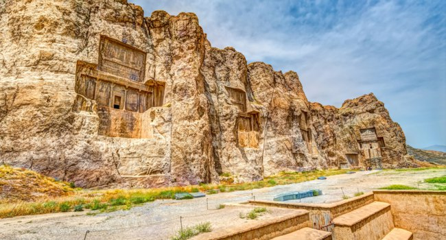 Иран. Накше-Рустам. Naqsh-e Rustam Panorama of the historical four tombs belonging to Achaemenid kings panorama view. Фото dbajurin - Depositphotos