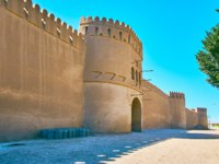 Иран. Крепость Раен. The view with a facade wall, gate and towers of ancient clay citadel of Rayen, Iran. Фото efesenko - Depositphotos