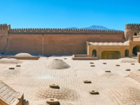 Иран. Крепость Раен. Restored courtyard of medieval Rayen Castle with domes of Governor's mansion, located on the lower level, Iran. Фото efesenko - Depositphotos