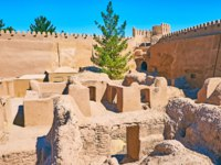 The small living buildings of ancient Rayen citadel are surrounded by huge adobe ramparts with watchtowers and battlements, Iran. Фото efesenko - Depositphotos