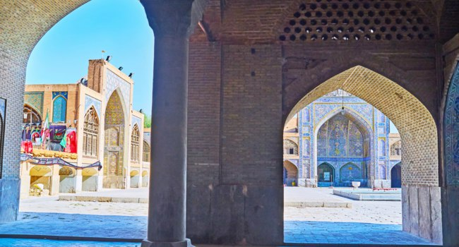 Иран. Исфахан. Мечеть Сейед. The brick arcade of Seyed Mosque opens the view on its courtyard with scenic portals, of bright tile in Isfahan. Фото efesenko - Depositp