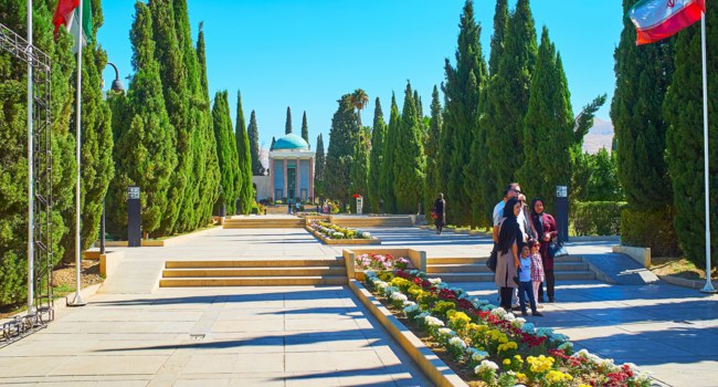 Иран. Шираз. The scenic garden with cypress alley and colorful flower beds at the site of Mausoleum of Persian poet Saadi in Shiraz. Iran. Фото efesenko - Depositphot