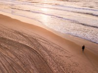 Израиль. Ашдод. Aerial view of lonely woman standing on empty sandy beach and looking at sunset, Ashdod, Israel. Фото VeronikaGorBO - Depositphotos