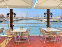 Израиль. Ашкелон. White tables and chairs of outdoor restaurant on promenade along marina on Mediterranean sea in Ashkelon, Israel. Фото rglinsky-Deposit