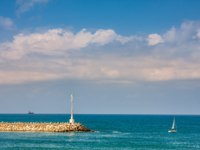 Израиль. Ашкелон. Beacon on breakwater and small yacht on Mediterranean sea along coast of Ashkelon, Israel. Фото rglinsky-Depositphotos