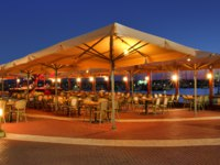 Израиль. Ашкелон. Illuminated outdoor restaurant on marina promenade on Mediterranean sea at evening in Ashkelon, Israel. Фото rglinsky-Depositphotos
