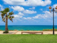 Израиль. Ашкелон. Stone bench between palm and decorative lamppost with beautiful view on Mediterranean sea. Ashkelon. Israel. Фото rglinsky-Depositphoto
