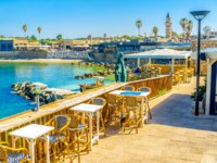 The outdoor restaurant in harbor of Caesaria overlooks the buildings, surrounding the port, bright blue water and tiny beach, Israel. Фото efesenko - Depositphotos