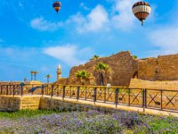 Израиль. Археологический парк Кесария. In the blue sky flies a colorful picturesque balloons. Ruins of the ancient city of Caesarea. Фото kavramm-Deposit