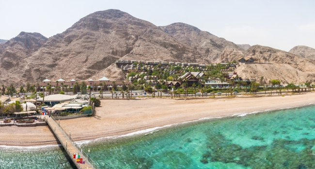 Израиль. Эйлат. Tower of Underwater Observatory Marine Park in Eilat. Desert mountains with hotels areas. Фото YKD - Depositphotos