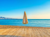 Израиль. Пляжи Эйлата. The lonely folded sunshade on the empty wooden terrace on the beach, Eilat, Israel. Фото efesenko - Depositphotos