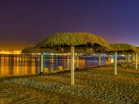 Израиль. Пляжи Эйлата. Night beach with the straw sunshades and bright reflection in water, Eilat, Israel. Фото efesenko - Depositphotos