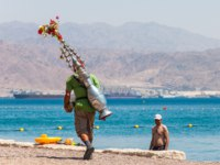 Израиль. Пляжи Эйлата. Man with red hat caring authentic tea vessel container on his back, on Eilat beach. Фото YKD - Depositphotos