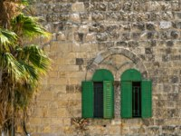 Израиль. Палестинские территории. Хеврон. Narrow arched windows with green iron shutters in stone wall of the old house. Фото ValenZi-Depositphotos