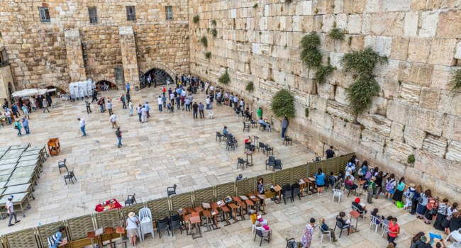 Prayers making their wishes and prays at the Western Wall, Wailing Wall or Kotel witch is located in the Old City, view from the Mughrabi Bridge. Фото dbajurin - Depositphotos