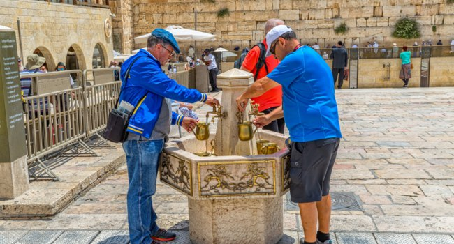 Ritual of hand at the Western Wall, Wailing Wall or Kotel witch is located in the Old City at the foot of the western side of the Temple Mount. Фото dbajurin-Depositphotos