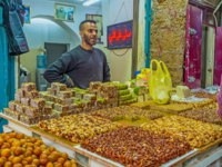 Израиль. Акко. The merchant in Turkish bazaar offers the tasty nuts' gozinaki, lokum, halva and other desserts in Acre. Фото efesenko - Depositphotos