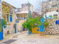 Израиль. Цфат. The tiny square at the entrance to the Galley Street with numerous Hebrew sign boards in Safed. Фото efesenko-Depositphotos