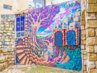 The colorful graffiti in branch of Gallery street depicts Safed, situated on the slope and surrounded by gardens and the Rabbi. Фото efesenko-Depositphotos