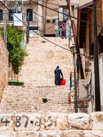 Клуб путешествий Павла Аксенова. Израиль. Цфат. Jewish orthodox with red bag go up the stairs in Old Town in Safed, Israel. Фото YKD-Depositphotos